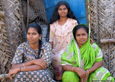 3 Tamil women in home made from woven coconut plam
